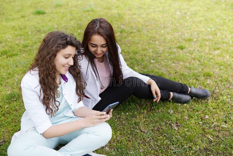 Женский студент докторов outdoors с телефоном медицинская предпосылка студенты около больницы в цветочном саде стоковое изображение