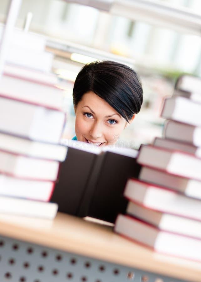 Женский студент окружен с кучами книг стоковое фото