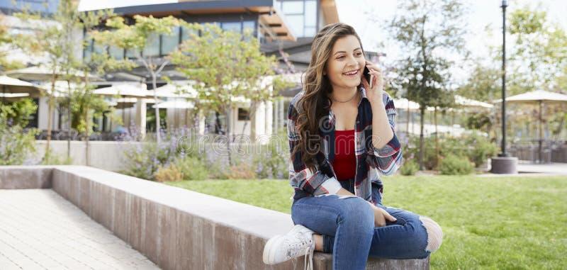 Женский студент средней школы говоря на мобильном телефоне вне зданий коллежа стоковое изображение rf