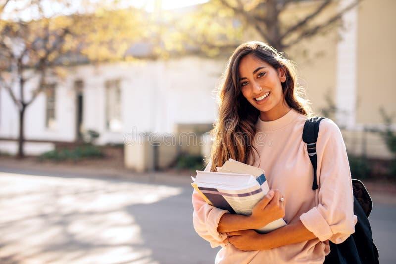 Женский студент колледжа с книгами outdoors стоковое изображение rf