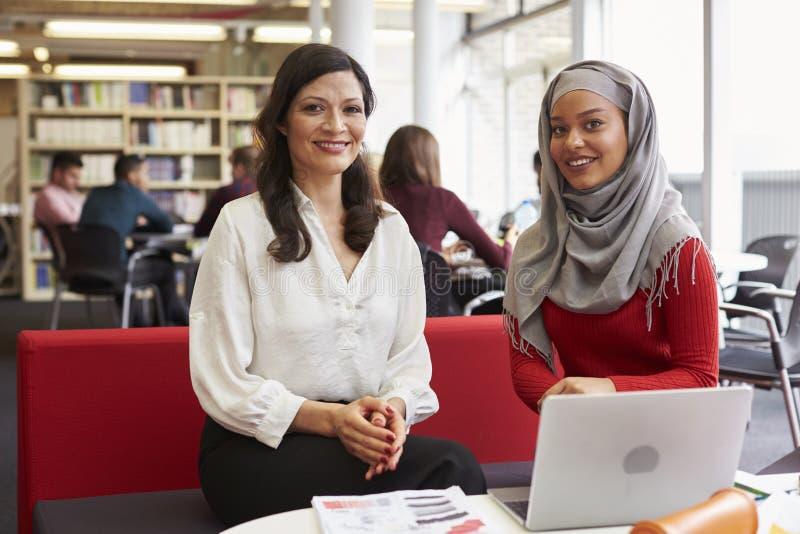 Женский студент университета работая в библиотеке с гувернером стоковые изображения
