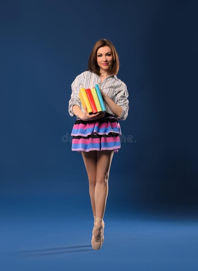 Женский танцор на цыпочках с кучей книг стоковые изображения rf