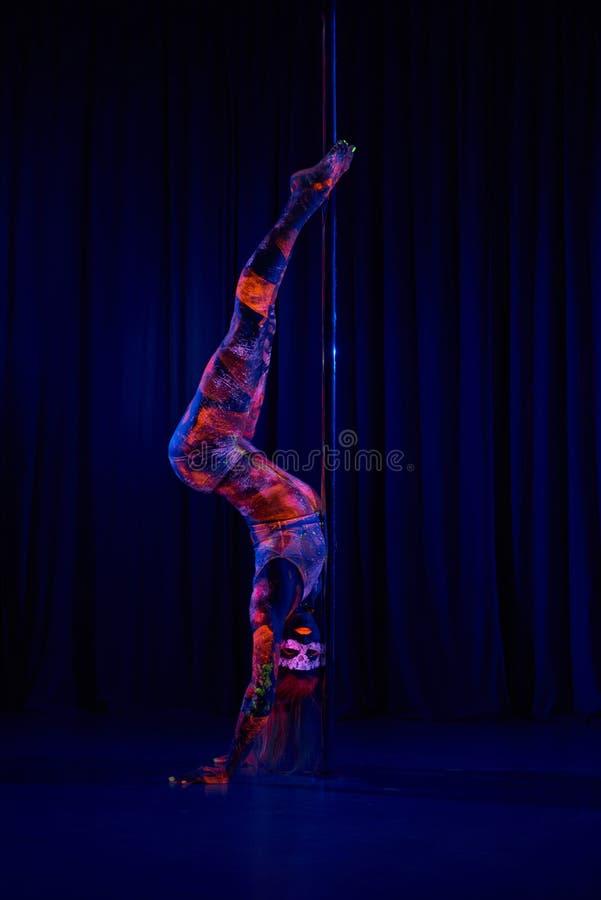 Женский танцор поляка в ярких неоновых цветах под ультрафиолетовым лучем стоковое фото rf