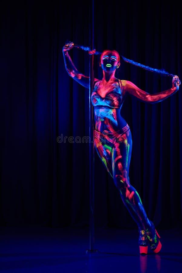 Женский танцор поляка в ярких неоновых цветах под ультрафиолетовым лучем стоковые изображения