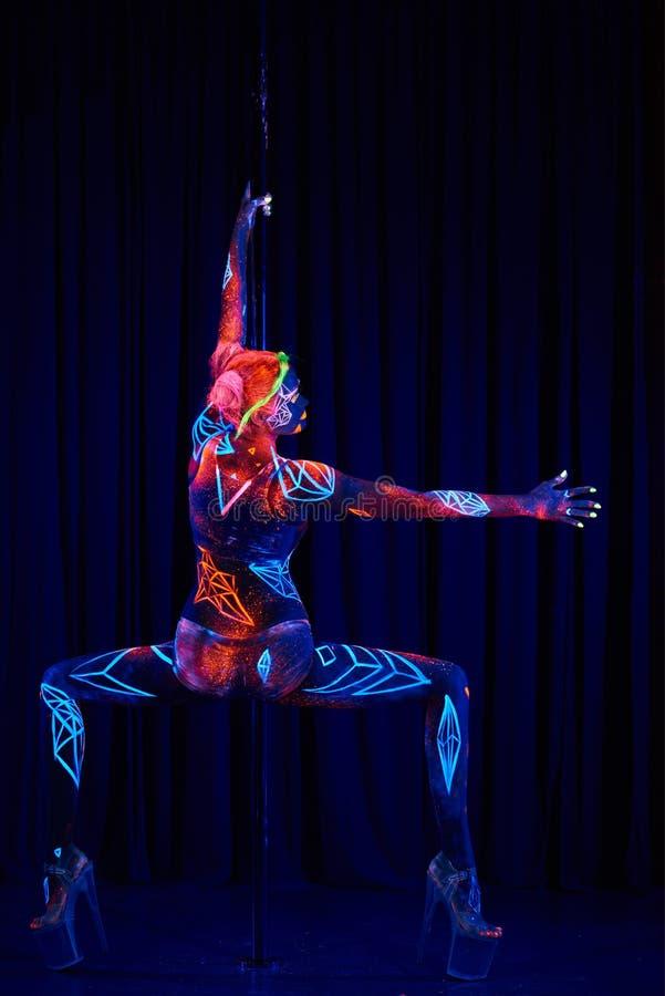 Женский танцор поляка в ярких неоновых цветах под ультрафиолетовым лучем стоковое фото