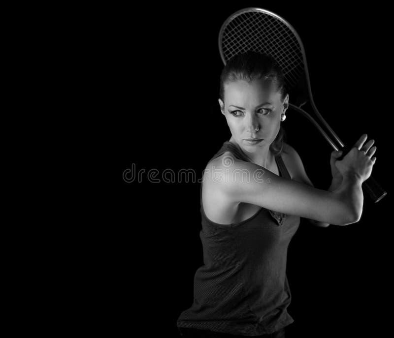 Женский теннисист с ракеткой готовой для того чтобы ударить стоковое фото