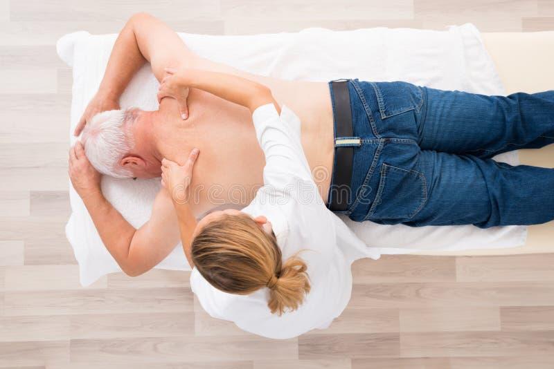 Женский терапевт давая массаж к старшему человеку стоковые изображения
