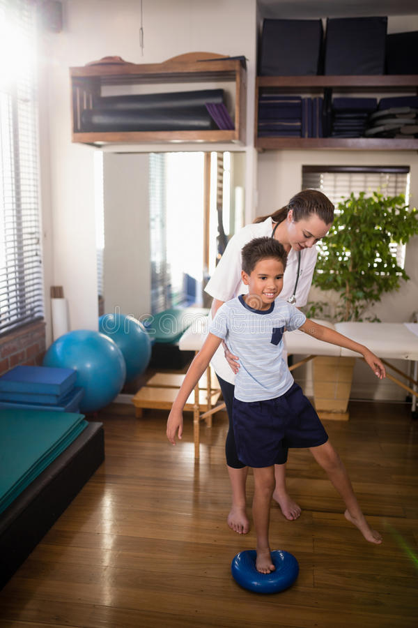 Женский терапевт держа мальчика стоя на голубом шарике стресса стоковое изображение