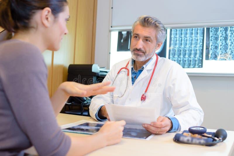 Женский терпеливый говорить к доктору стоковая фотография