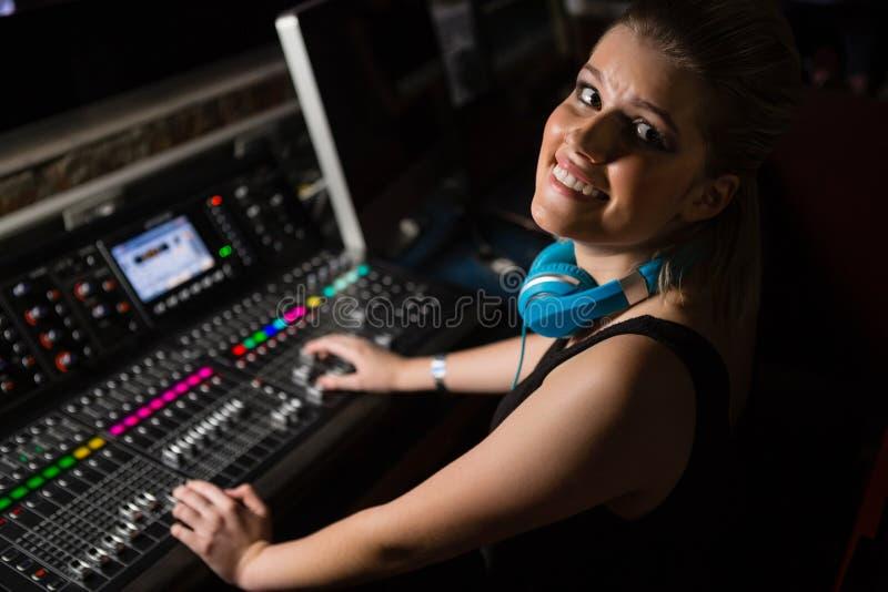 Женский тональнозвуковой инженер используя ядровый смеситель в студии звукозаписи стоковые фото