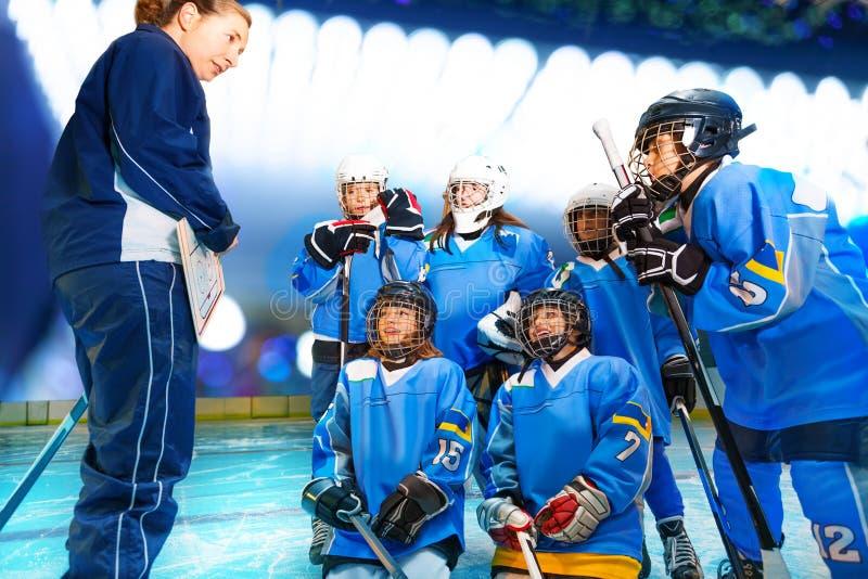 Женский тренер и хоккейная команда обсуждая стратегию игры стоковое фото rf