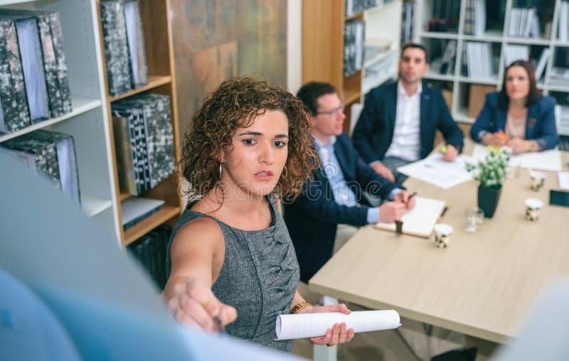 Женский тренер объясняя проект к команде дела стоковые фото