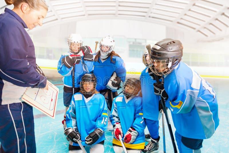 Женский тренер объясняя стратегию к хоккейной команде стоковое фото