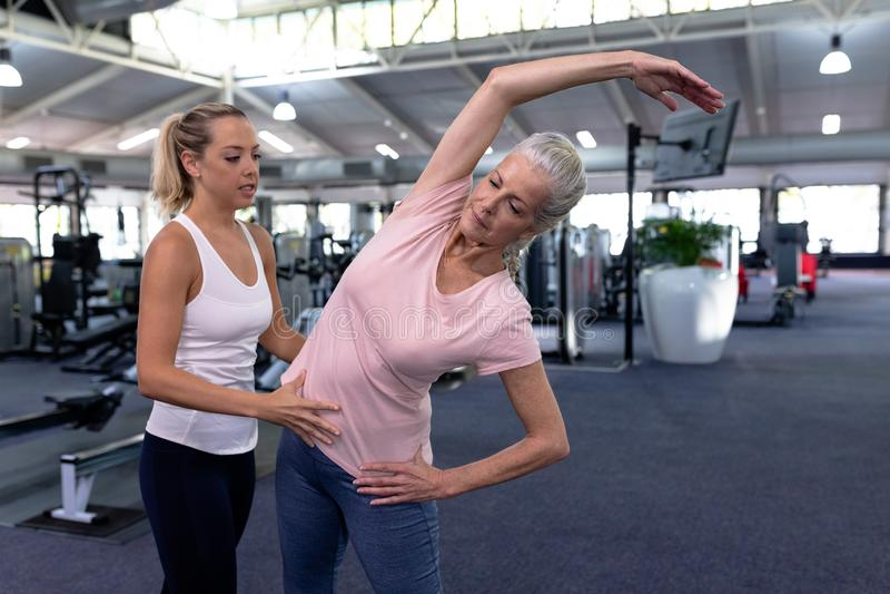 Женский тренер помогая активной старшей женщине в современном спортивном центре стоковая фотография