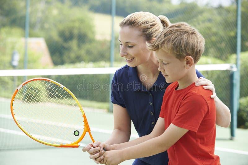 Женский тренер по теннису давая урок к мальчику стоковые фотографии rf