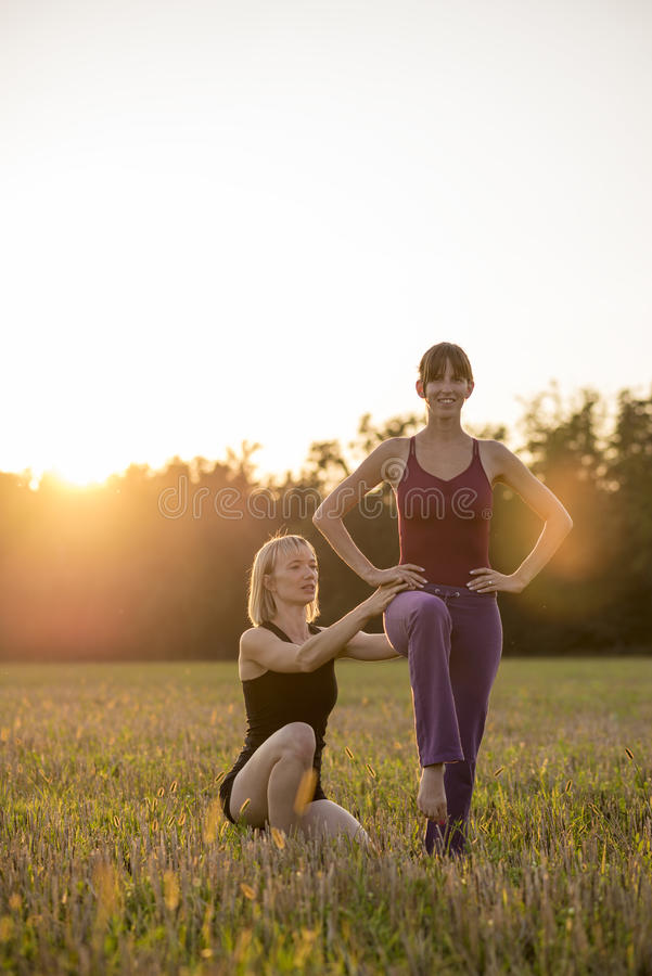 Женский тренер pilates делая коррекции к ее тренирующей как они стоковое фото