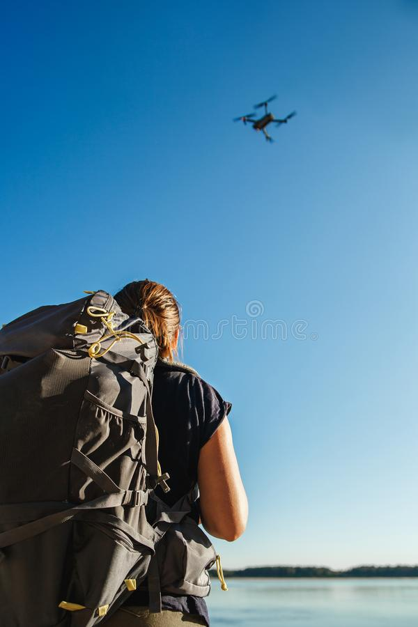 Женский турист контролируя трутня с дистанционным управлением Положение берега реки стоковое изображение rf