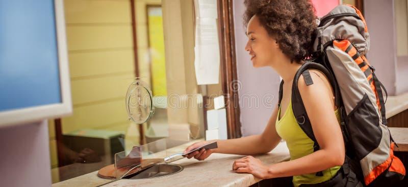 Женский турист покупает билет на кассе конечной станции стоковая фотография