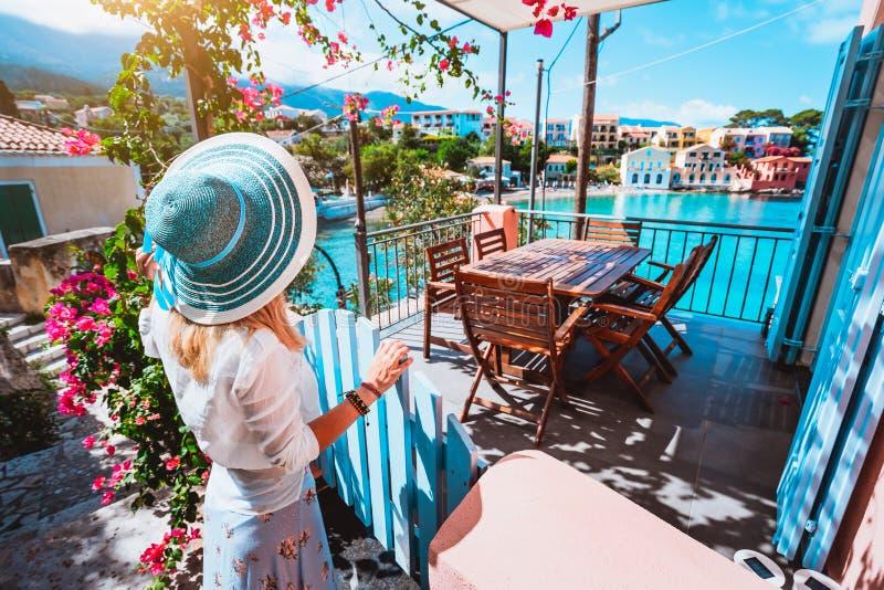 Женский турист с голубой шляпой солнца оставаясь в деревне Assos перед уютной верандой и восхищая залива покрашенного бирюзой  стоковая фотография