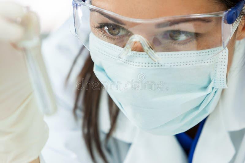 Женский ученый исследования женщины с пробиркой в лаборатории стоковое фото