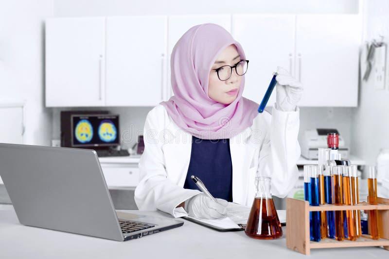 Женский ученый проверяя пробирку стоковые фото