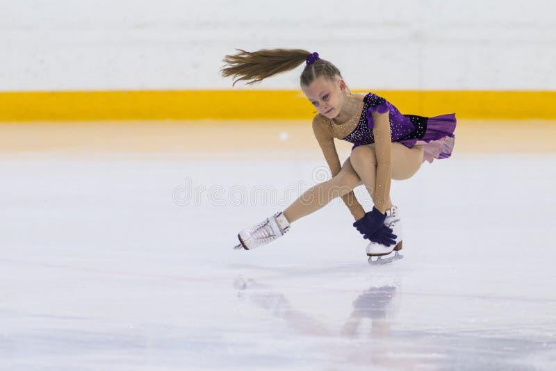 Женский фигурист от Беларуси Nadezhda Shatravskaya выполняет программу девушек Cubs b свободную катаясь на коньках на чашке арены стоковые изображения