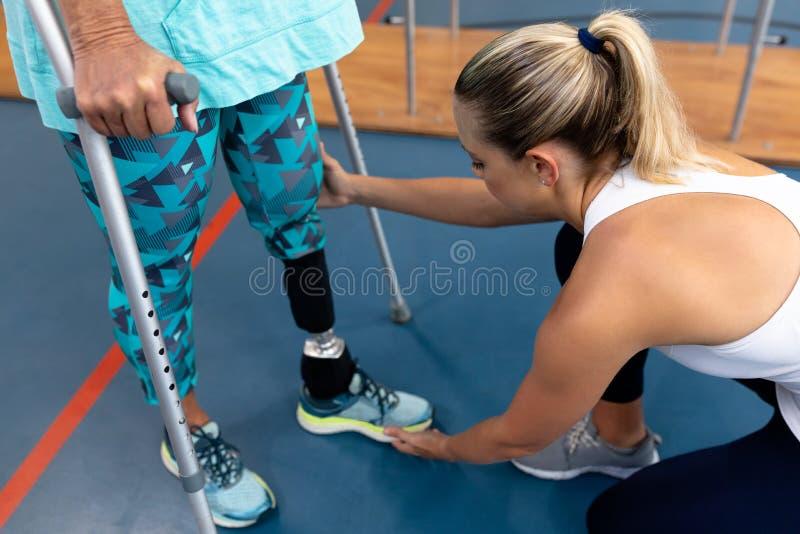 Женский физиотерапевт помогая неработающей старшей прогулке женщины с костылями локтя в спортивном центре стоковое изображение rf