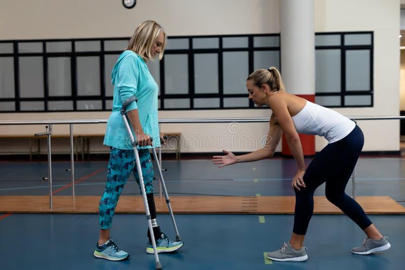 Женский физиотерапевт помогая неработающей старшей прогулке женщины с костылями локтя в спортивном центре стоковое изображение