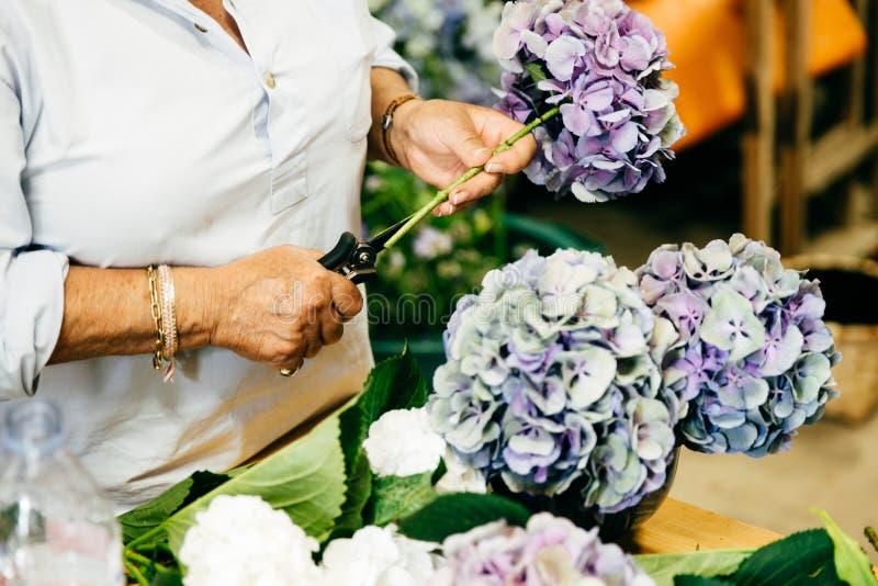 Женский флорист делая красивые bouquetes пока стоящ на цветочном магазине Непознаваемая персона создавая bouquetes чудесного flo стоковые изображения rf