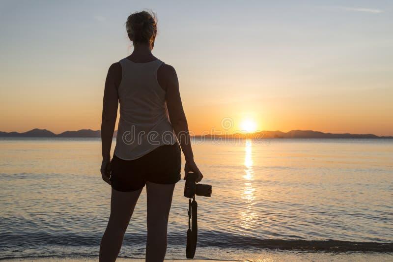 Женский фотограф морем на заходе солнца стоковое фото rf