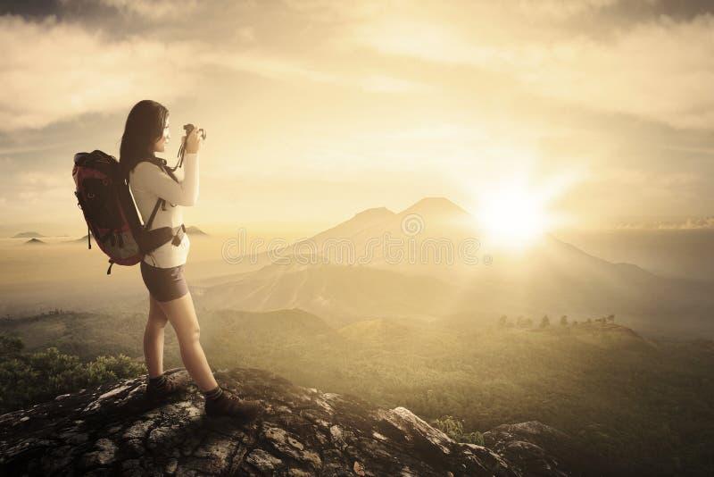 Женский фотограф принимает фото в горном пике стоковое изображение