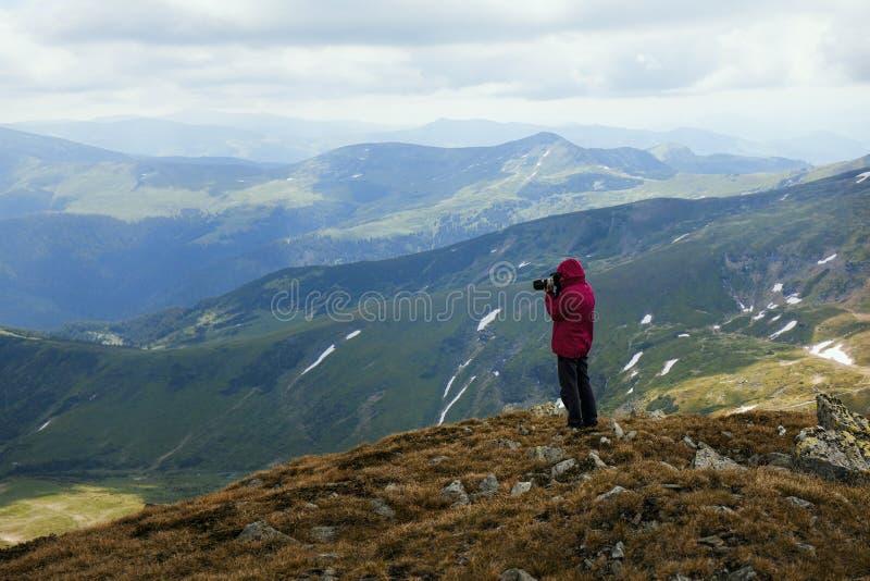 Женский фотограф силуэта в действии большие горы горы ландшафта съемка природы стоковая фотография