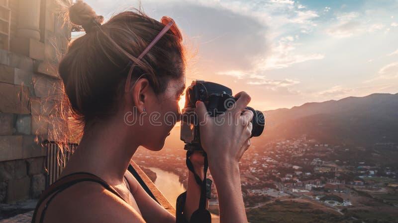 Женский фотограф, фотографируя ландшафт горы на заходе солнца стоковые фотографии rf