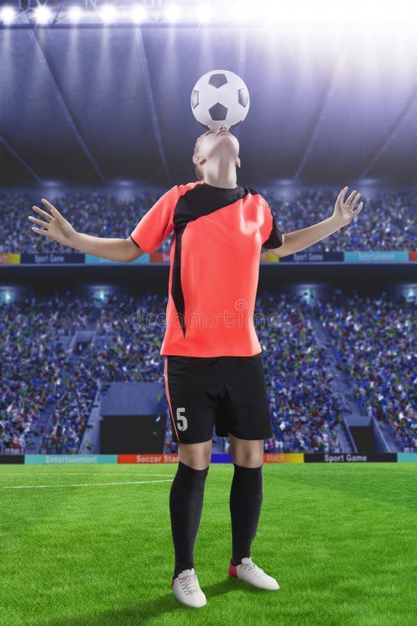 Женский футболист в красном равномерном делая фокусе с шариком стоковые фото