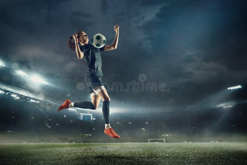Женский футболист пиная шарик на стадионе стоковое фото rf