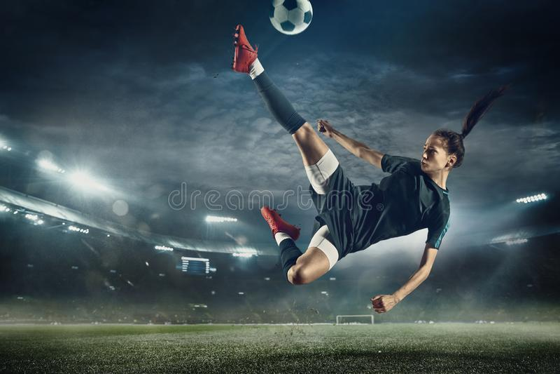 Женский футболист пиная шарик на стадионе стоковые изображения rf