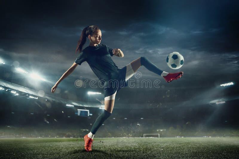 Женский футболист пиная шарик на стадионе стоковая фотография