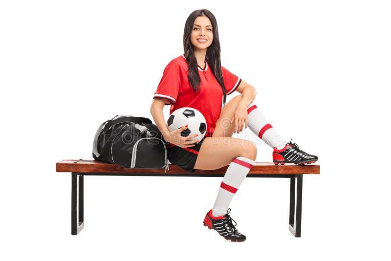 Женский футболист сидя на стенде стоковое фото