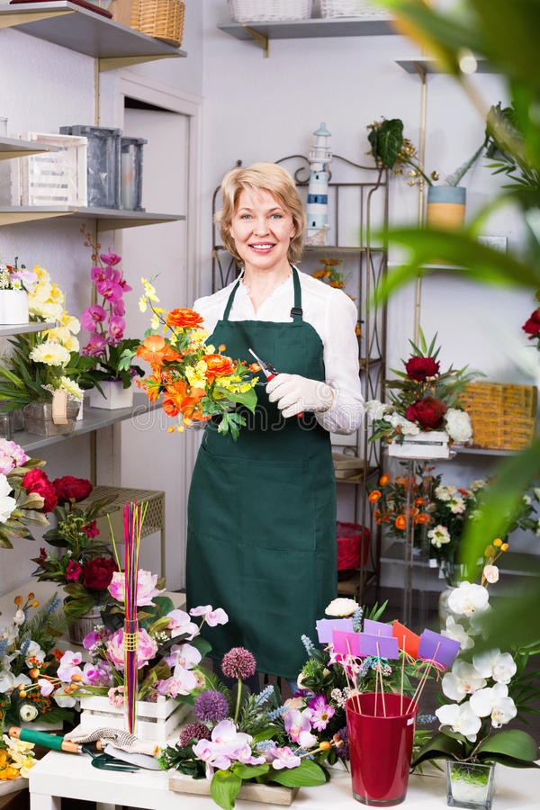 Женский флорист нося рисберму и счастливо подготавливая цветки стоковая фотография rf
