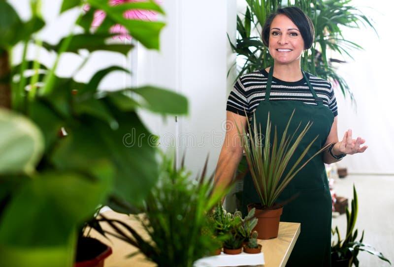 Женский флорист нося рисберму и счастливо работая стоковое изображение