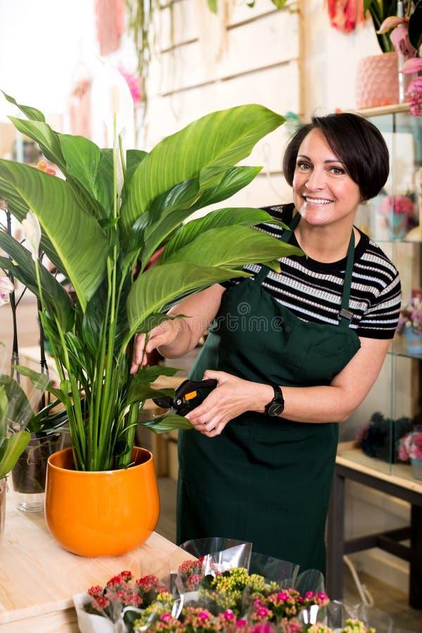 Женский флорист нося рисберму и счастливо работая стоковые фото