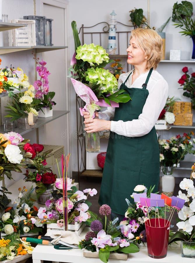 Женский флорист нося рисберму и счастливо стоя среди flowe стоковые изображения rf