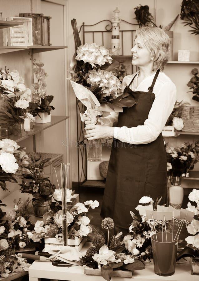Женский флорист нося рисберму и счастливо стоя среди flowe стоковая фотография