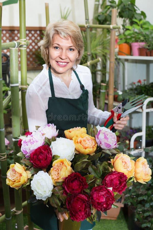 Женский флорист счастливо держа большой букет с пионами стоковое фото