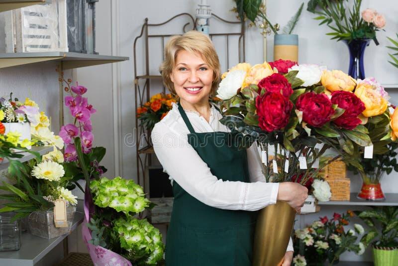 Женский флорист счастливо держа большой букет с пионами стоковые фото