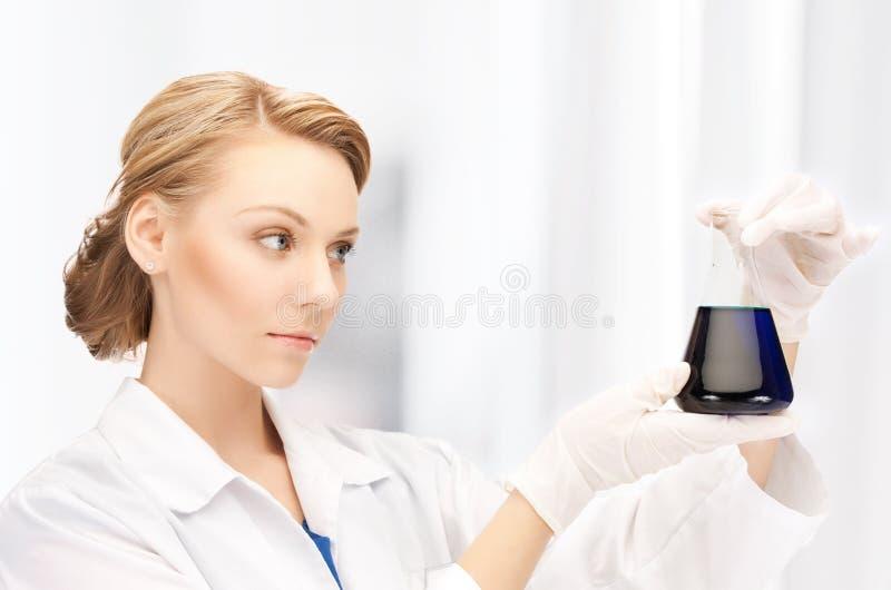 Женский химик держа шарик с химикатами стоковое изображение
