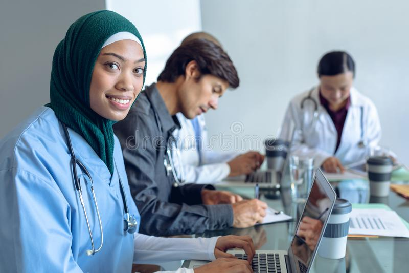 Женский хирург в hijab смотря камеру пока используя ноутбук на таблице в больнице стоковая фотография rf