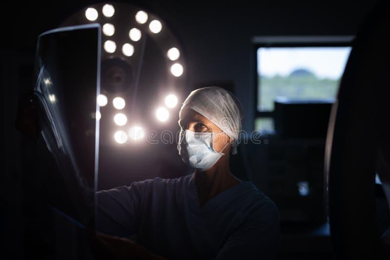 Женский хирург смотря изображение рентгеновского снимка в комнате деятельности стоковое фото rf