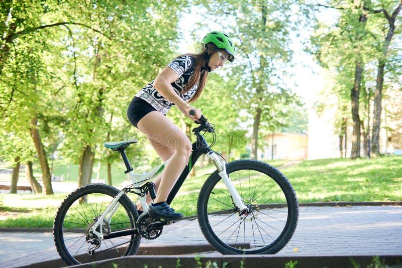 Женский холм велосипеда катания велосипедиста вверх вымощенный стоковая фотография rf