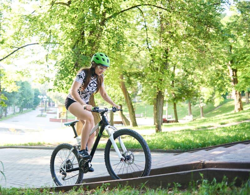 Женский холм велосипеда катания велосипедиста вверх вымощенный стоковая фотография